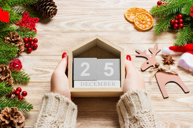 Вид сверху женских рук, держащих календарь