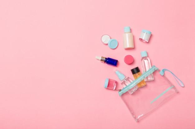 ピンクの背景に旅行するための小瓶のグループ。アイデア用のスペースをコピーします。化粧品のフラットレイ組成。コットンパッド付きクリームコンテナーの平面図
