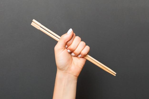 箸を持つ女性の手。あなたのデザインの空スペースで中華料理のコンセプト