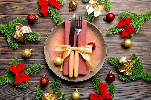 Вид сверху новогодний ужин на праздничный деревянный стол. состав тарелки, вилки, ножа, елки и украшения. с рождеством христовым концепция