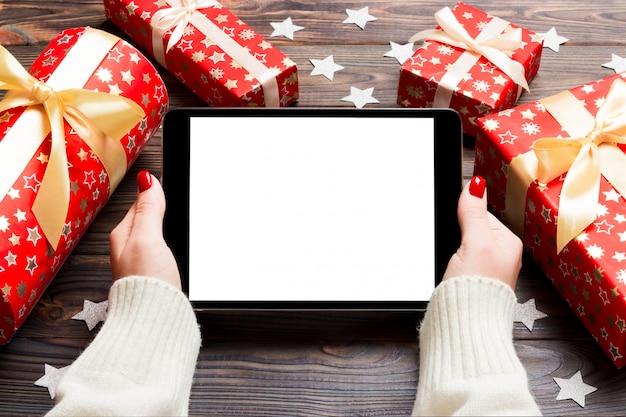 ギフト用の箱と雪で作られた木製のクリスマス背景にタブレットを保持している女性の手の平面図です。新年の休日の概念。