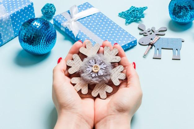 女性の手で雪の結晶の平面図。クリスマスの飾り。新年の休日の概念