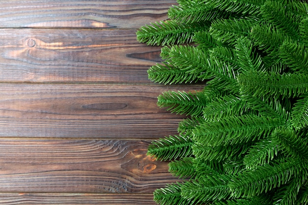 Взгляд сверху рамки сделанной из ветвей ели на деревянной предпосылке. рождество концепция с пустым пространством для вашего дизайна