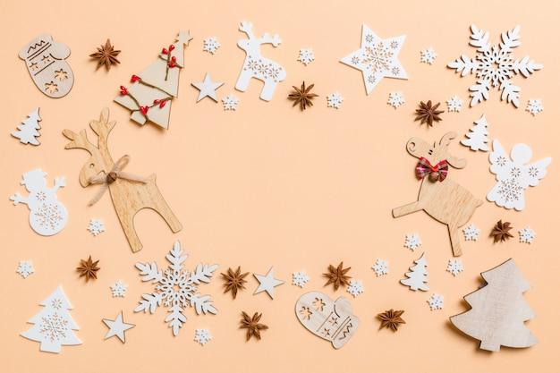 お祝いデコレーションとオレンジ色の背景のおもちゃ。コピースペースでメリークリスマスコンセプト