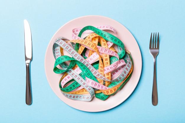 丸皿のスパゲッティの代わりにカラフルな測定テープのヒープ。健康的な食事の概念のトップビュー