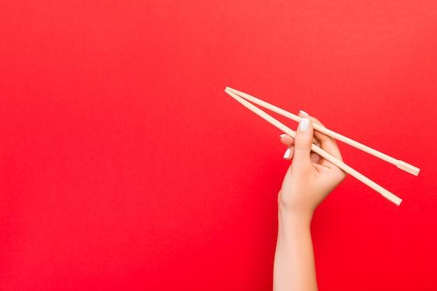 赤の背景に箸を持っている女性の手。あなたのデザインの空スペースで中華料理のコンセプト