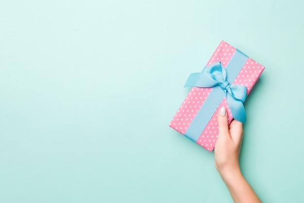 女性の手は、色とりどりの紙に包まれたクリスマスや他の休日の手作りプレゼントを与えます。プレゼントボックス、青いテーブル、コピースペースと平面図上のギフトの装飾