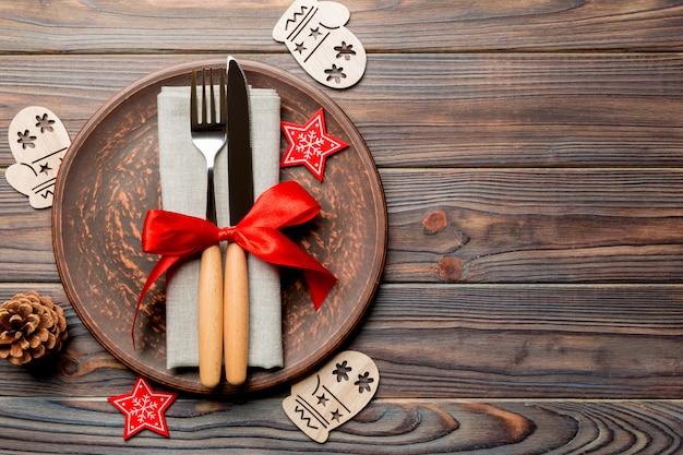 Вид сверху тарелки, вилки и ножа подается на украшенный рождеством деревянный стол