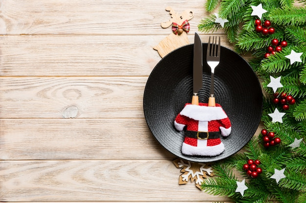 木製のテーブルでクリスマスディナーの平面図です。コピースペースとプレート、調理器具、モミの木、休日の装飾