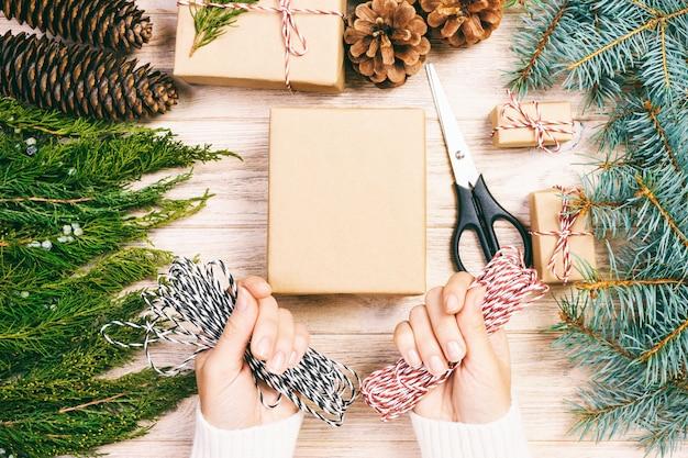 クリスマスプレゼントを包む女性、女の子はモミの木と松ぼっくりでクリスマスプレゼントを準備します。手作りのギフト