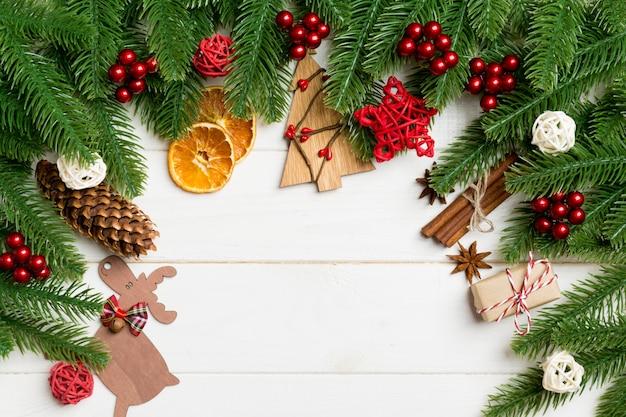 モミの木の枝と木製のお祝いの装飾的なおもちゃの平面図です。