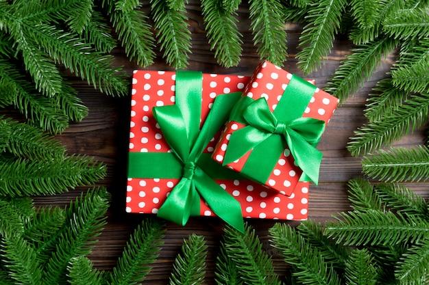 Взгляд сверху коробки подарков украшенной с рамкой сделанной из ели на деревянном.