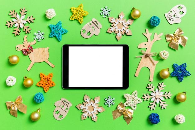新年のおもちゃや装飾品と緑のデジタルタブレットのトップビュー