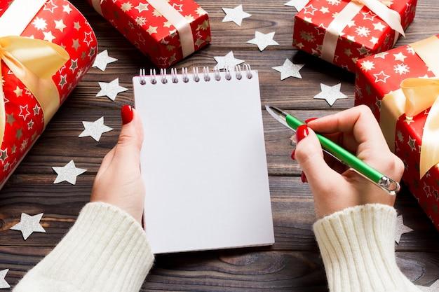 木製のクリスマスにノートに書く女性の手の上から見る。
