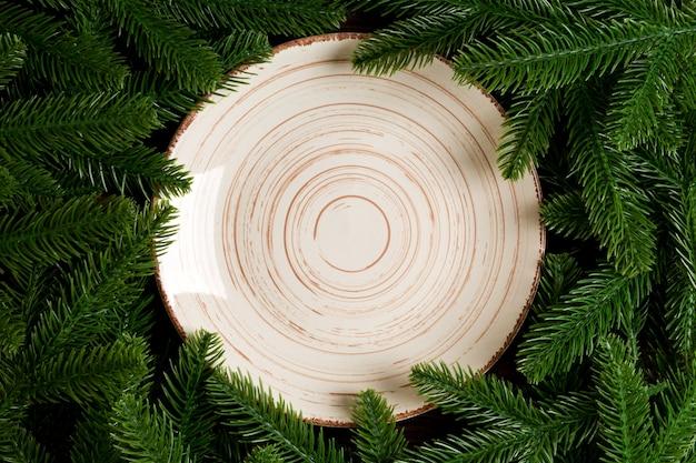 Взгляд сверху белой плиты окруженное с ветвями ели.