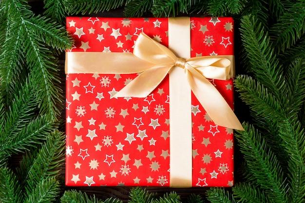 Взгляд сверху коробки подарка к празднику и ветвей ели с пустым космосом для вашего дизайна.