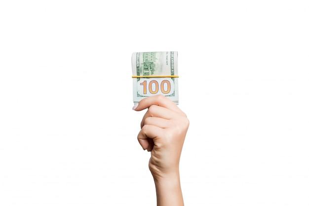 Изолированное изображение женской руки держа пачку долларов на белизне.