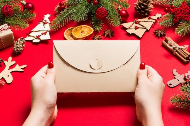 休日の装飾で作られた赤の封筒を保持している女性の平面図です。