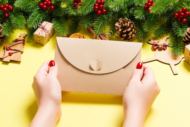 休日の装飾で作られた黄色の封筒を保持している女性の平面図です。