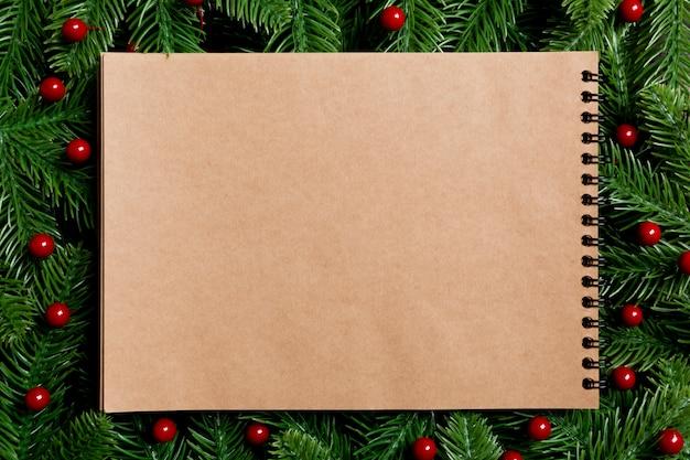 木製のモミの木で作られたフレームを飾ったクラフト紙で作られたトップビューのノートブック。時間