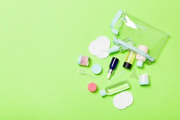 Вид сверху средства по уходу за лицом: флаконы и баночки с тоником, мицеллярная очищающая вода, крем, ватные диски на зеленый. уход за телом