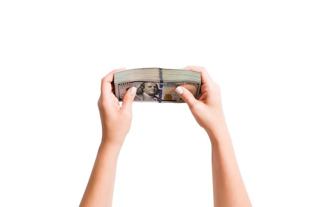 Вид сверху пачка денег в женских руках. изображение подсчитывая доллары на изолированной белизне. налог