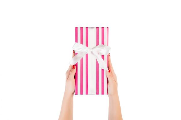 女性の手は、ピンクの紙の白いリボンで包まれたクリスマスや他の休日の手作りプレゼントを与えます。白、トップビューで分離されました。感謝祭ギフトボックス