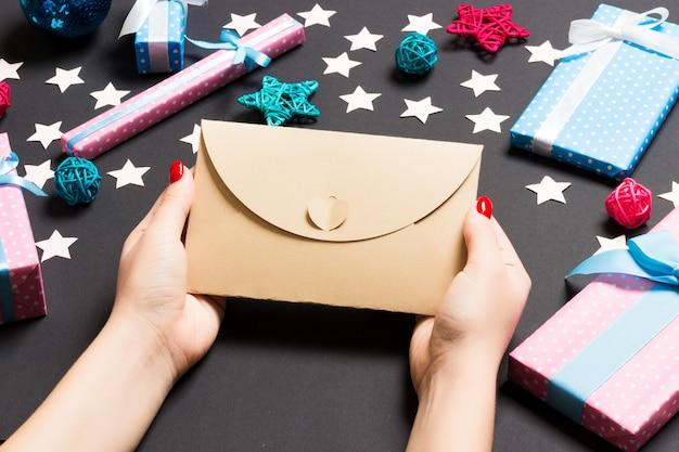 黒の封筒を保持しているトップビュー女性は、休日の装飾を作った。クリスマスの時期