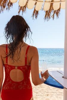 水のボトルを保持しているビーチに赤い水着の若い女性