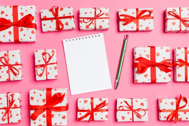 あなたのデザインの空スペースでカラフルな背景に赤いハートのノートブックとギフトボックスの休日組成。バレンタインデーのコンセプトのトップビュー