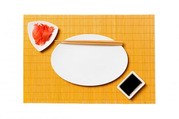 Пустая овальная белая тарелка с палочками для суши и соевым соусом