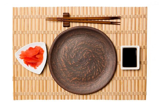 寿司と醤油の箸で空の丸い茶色のプレート