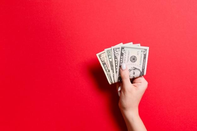 しっかりとお金の束を持っている女性の手。カラフルな背景の異なるドルの平面図。コピースペースの投資コンセプト
