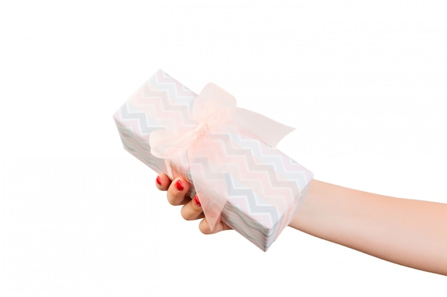 Женские руки дарят завернутый рождественский или другой праздничный подарок ручной работы из цветной бумаги с оранжевой ленточкой