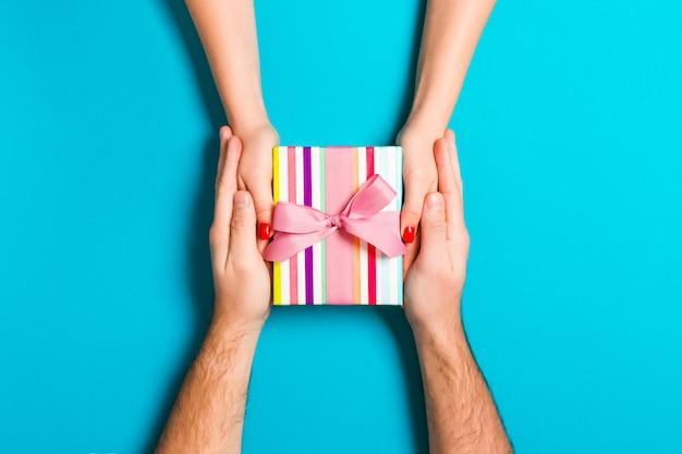 男と女のカラフルな背景に休日の贈り物を授受の平面図