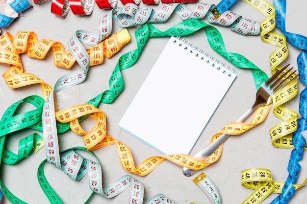 カラフルな測定テープ、フォーク、セメントの背景にメモ帳の構成