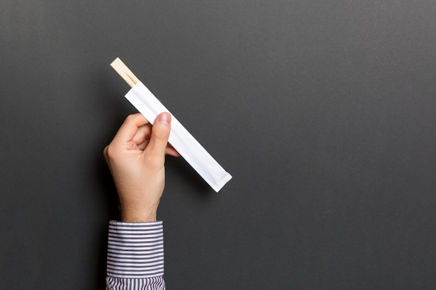 黒い背景に箸を持っている男性の手の画像をトリミングします。