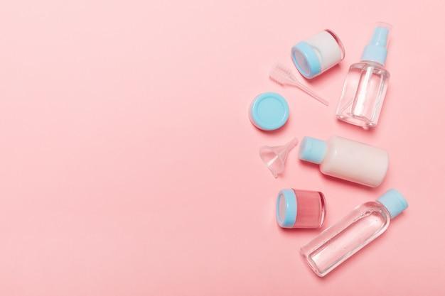 Вид сверху композиция маленьких дорожных бутылок и баночек для косметических продуктов на розовом фоне