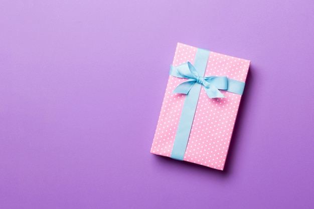 Завернутый подарок на рождество или другой праздник ручной работы в бумаге с голубой лентой на фиолетовом фоне