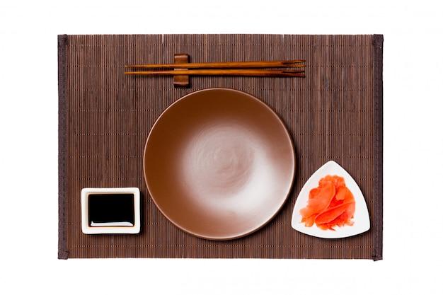 Пустая круглая коричневая тарелка с палочками для суши