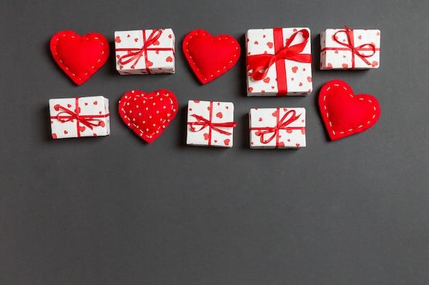 Взгляд сверху красочной валентинки сделанной из подарочных коробок и красных текстильных сердец. день святого валентина
