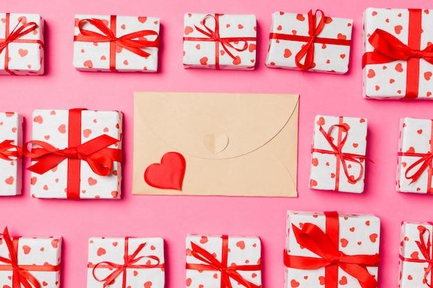 Взгляд сверху красочной валентинки сделанной из конверта ремесла, подарочных коробок и красных текстильных сердец. день святого валентина