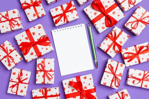 バレンタインの日のカラフルな平面図に赤いハートのノートとギフトボックスの休日組成