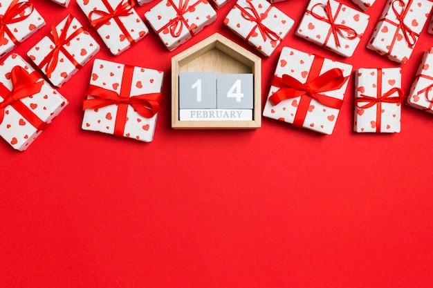 Праздничная композиция из подарочных коробок с красными сердечками и деревянного календаря на разноцветных четырнадцатого февраля. вид сверху на день святого валентина