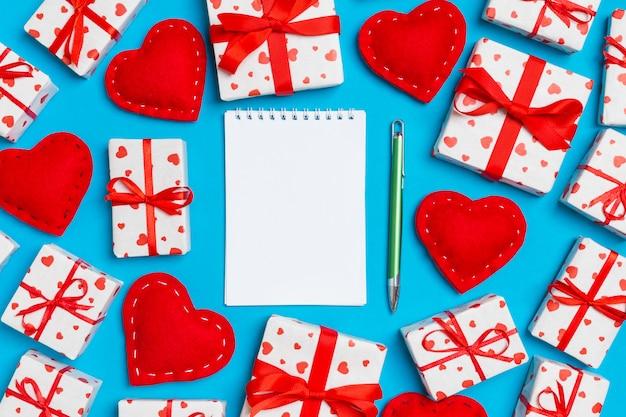 カラフルなノート、白いギフトボックス、赤い繊維の心の平面図です。バレンタイン・デー