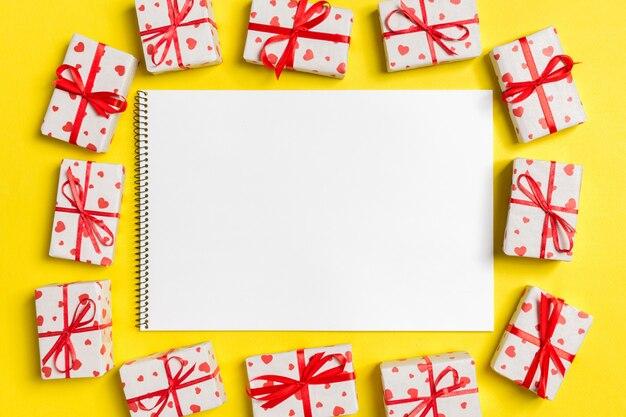 カラフルな背景のギフトボックスに囲まれたノートブックの平面図です。バレンタイン・デー