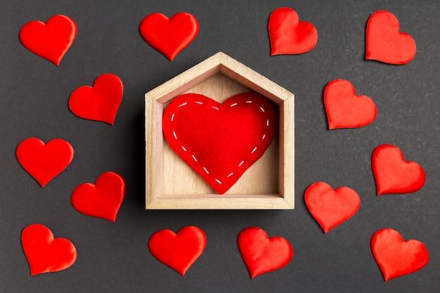 カラフルな背景に小さなハートで飾られた木造住宅の赤いハートのクローズアップ。バレンタイン・デー。ホームスイートホームコンセプト