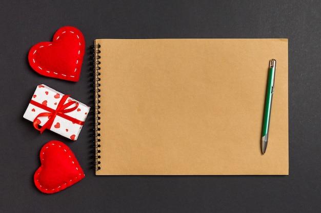 テーブルの上の心とギフトボックスに囲まれたクラフトノートの平面図です。バレンタイン・デー