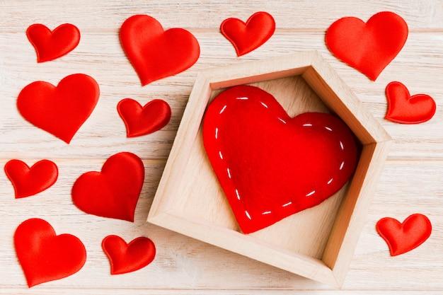 木製の背景に小さな心に囲まれた家で赤いハートのトップビュー構成。ホームスイートホームコンセプト。バレンタイン・デー