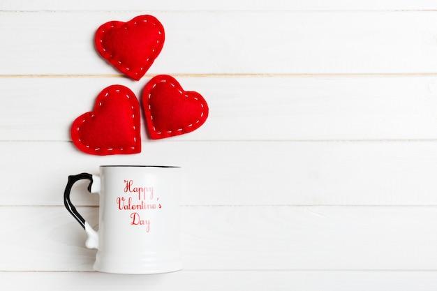 木製の背景の上にカップからはね心の平面図構成。愛とロマンスのコンセプト。バレンタイン・デー
